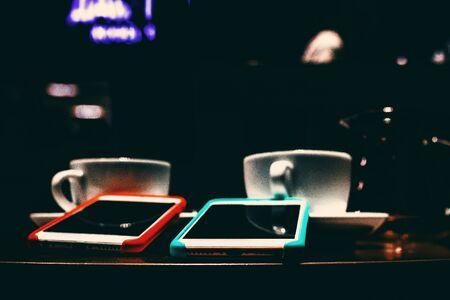 Two smartphone closeup. Cafe, coffee, dark scene.