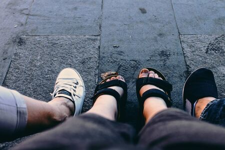 Four legs, 3 person. Shoes on the road.