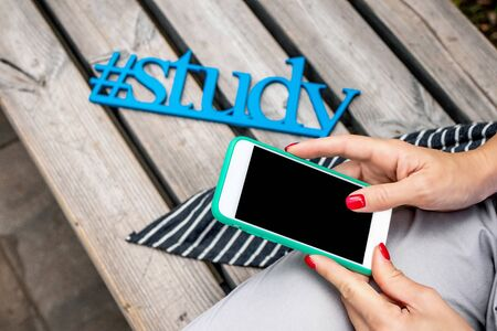 Wooden word study close to woman with smartphone. Letters study, blue letters.