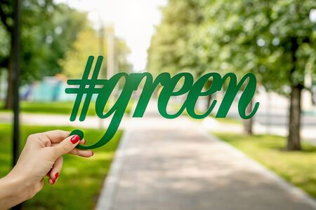 Green letters in woman hand in the park, green background. City background, alphabet, organic.