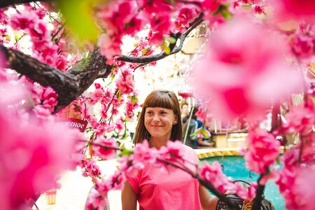 Portrait of woman among sakura tree in the shopping mall.