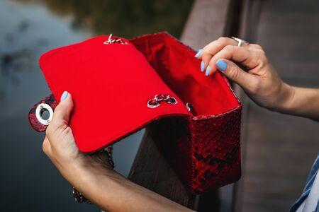 Stylish woman with snakeskin handbag outdoors. Fashion bag.