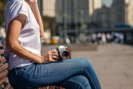 Woman holding retro vintage camera outdoors. Old camera. Beautiful female photography.