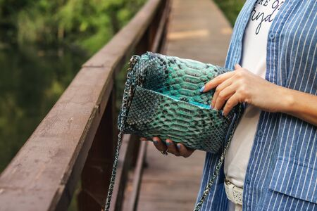 Stylish woman with snakeskin handbag outdoors.