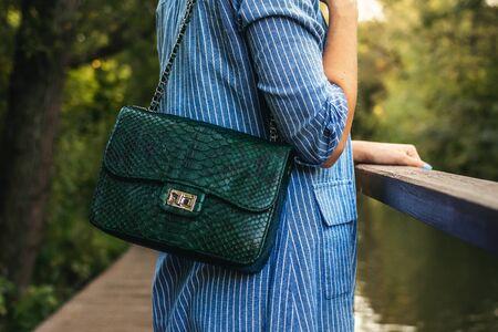 Stylish woman with snakeskin handbag outdoors.
