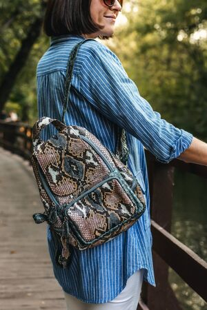 Young stylish woman with snakeskin python backpack.