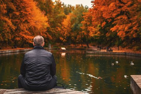 Alone man sits beside a pond in the park. Autumn background. Water, landscape.