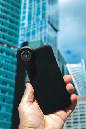 Man hand holding smartphone on a skyscraper background. Corporate stock image.