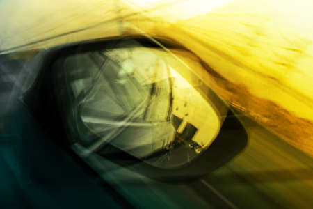 Car side mirror. Abstract photography. Rush concept. Sunset time.
