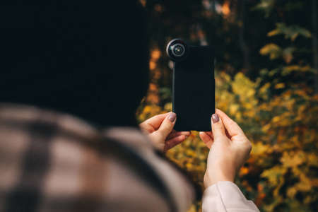 Woman holds smartphone with additional lens on an autumn background. Standard-Bild