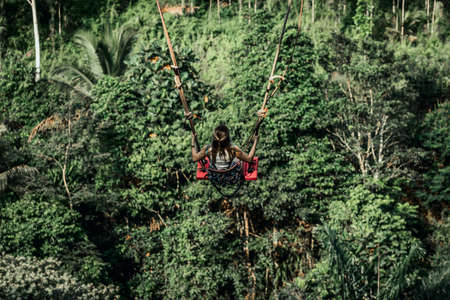 Young woman swings in the jungle of Bali island. Rainforest of Indonesia. Travel concept.