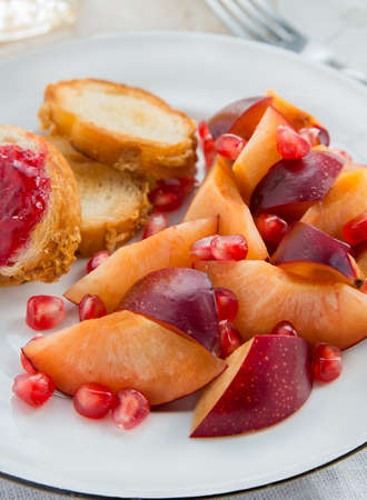 Sliced plum and pomegranate seeds on plate photo