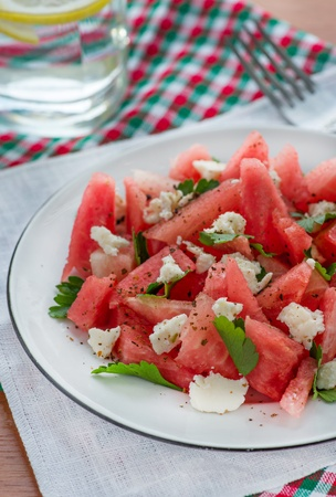 Watermelon salad with feta cheese and parsley, closeup, glass of water behind photo