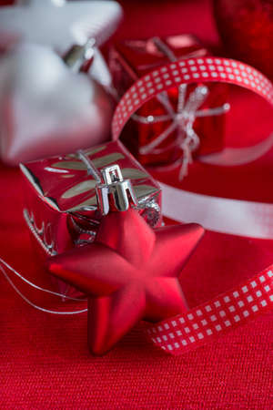 Star-shaped Christmas decorations with ribbon on red background, closeup photo