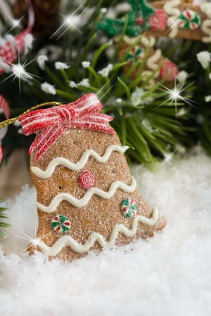 Christmas bell decoration in the shape of Gingerbread cookie on snow photo