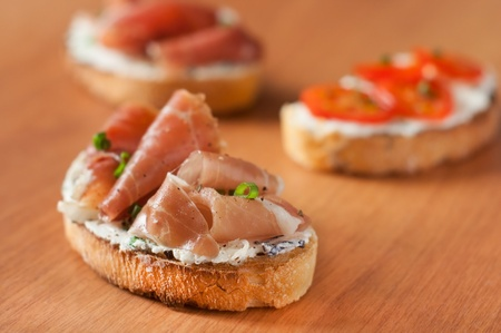 Bruschetta with goat cheese and prosciutto, selective focus photo