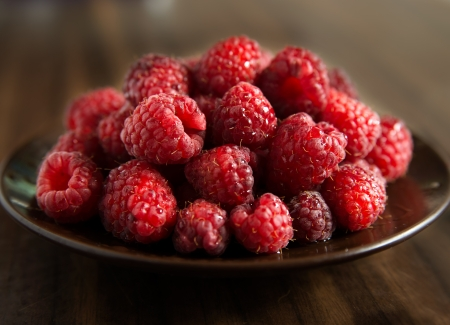Fresh raspberries on brown plate, dark background, selective focus Stock Photo - 18574983