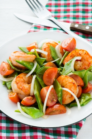 Snow peas and tomato salad with shrimps (prawns), vertical photo