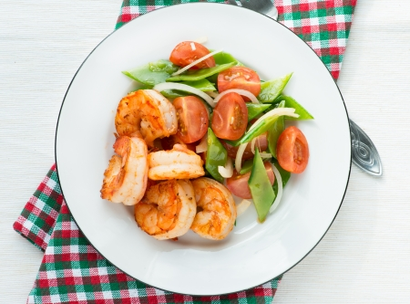 Shrimps (prawns) and fresh snow peas and tomato salad, overhead photo