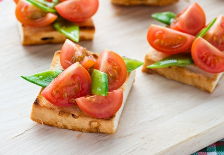catering food: Bruschetta with fresh tomato and snow peas, selective focus