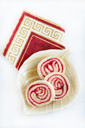Strawberry and lemon jam swiss roll on plate over light background photo