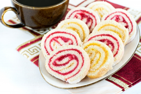 Strawberry and lemon jam swiss roll with cup of coffee, selective focus photo