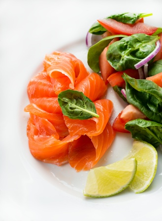 Salted salmon with fresh green salad and lime, selective focus photo