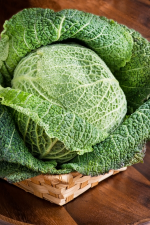 Wet savoy cabbage in basket over wooden  background, selective focus photo