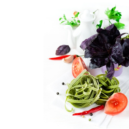 Uncooked spinach pasta with tomatoes, herbs, spices and oil jug, copy space, selective focus photo