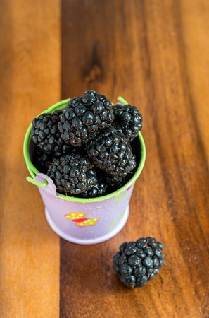 Fresh blackberries in a decorative bucket, selective focus photo