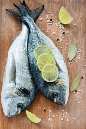 food fish: Fresh dorada fish with sea salt, lime and bay leaf over wooden background