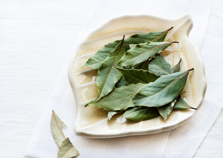 Bay leaves on plate over light background, selective focus Stock Photo