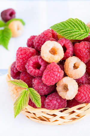 Mixed raspberries in basket over light background, closeup, selective focus photo