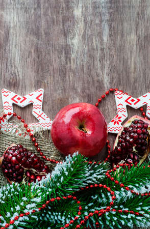 Pomegranate, apple with festive decorations over wooden background, selective focus, copy space photo