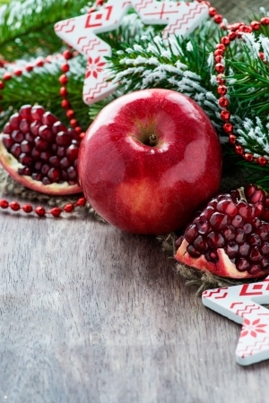 Pomegranate and apple with festive decorations over wooden background, selective focus, copy space photo