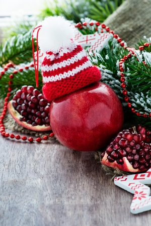 Red apple in hat and pomegranate with festive decorations over wooden background, selective focus, copy space photo