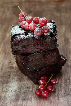 flourless chocolate cake: Chocolate brownie with cherries over wooden background, selective focus