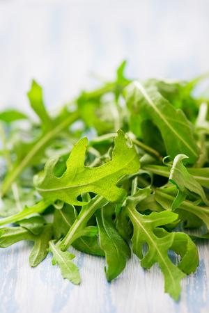 Fresh arugula over light  background, selective focus Stock Photo