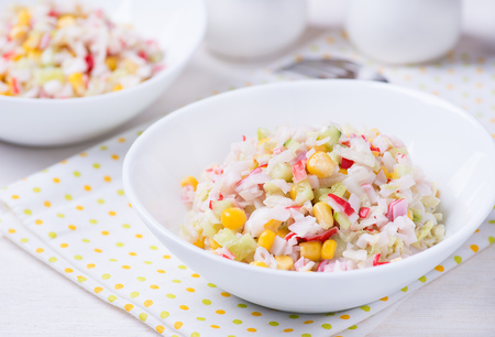 Fresh vegetable salad with corn, cabbage, crab and mayonnaise, selective focus photo