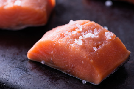 Raw red fish fillet with sea salt on dark pan, close up, selective focus