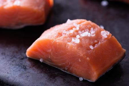 dog salmon: Raw red fish fillet with sea salt on dark pan, close up, selective focus