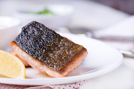 dog salmon: Grilled red fish fillet with lemon and green salad, close up, selective focus