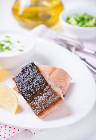 dog salmon: Grilled red fish fillet with lemon and yogurt sauce, selective focus