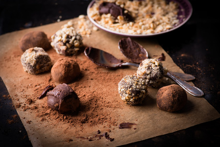 truffles: Assorted dark chocolate truffles with cocoa powder, biscuit and chopped hazelnuts over baking paper, selective focus