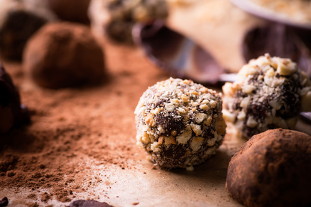 truffles: Assorted dark chocolate truffles with cocoa powder, biscuit and chopped hazelnuts over baking paper, selective focus, close up