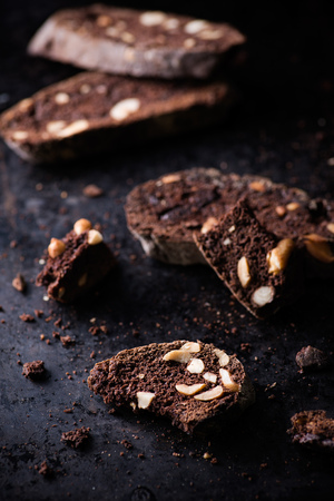 chocolate chip cookie: Dark chocolate biscotti with nuts on baking paper, selective focus Stock Photo