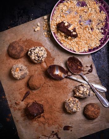 cioccolato natale: Assortiti tartufi di cioccolato fondente con cacao in polvere, biscotti e le nocciole tritate su carta da forno, messa a fuoco selettiva, vista dall'alto