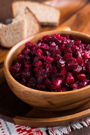 russian salad: Russian beetroot salad in wooden bowl with rye bread, rustic, close up, selective focus Stock Photo