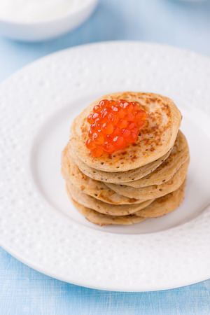 maslenitsa: Buckwheat blini with red caviar on white plate, selective focus