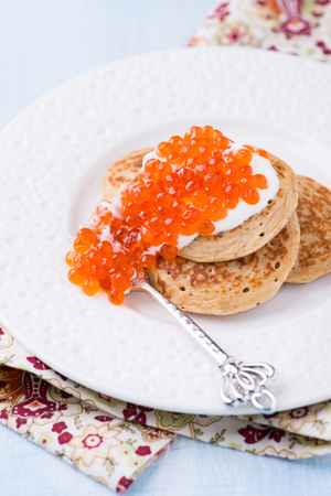 blini: Buckwheat blini with red caviar and sour cream on white plate, selective focus Stock Photo